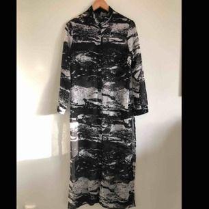 Snygg, lång genomskinlig skjorta!  Melerad svart/vit.  På mig räcker den ner till anklarna och jag är 165cm.  Knäppning 2/3 uppifrån. Några decimeter slitsad i sidorna.  Perfekt på sommaren!