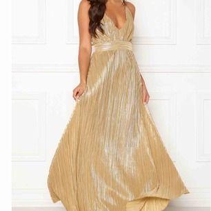 Färg: Guld. Material: 100% polyester. Modellens längd & Storlek: 173cm | Small. Skimrande långklänning från Make Way. Tillverkad i en stum kvalitét som har en vecker plissering och faller fint. Dold dragkedja i ryggen.