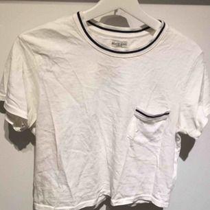 Croppad t-shirt med mörkblå detaljer i kragen och på fickan. Använd ca 2 gånger.
