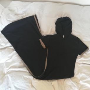 Svart/beige sportig långklänning med stripe längs sidan köpt secondhand men från H&M från början. Ovanlig modell med luva och dragkedja. Stl 38. Längd 140 cm mätt från nacken. Frakt 59 kr.