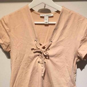 T-shirt med snörning vid bysten. Super fin beige/rosa färg. Använd fåtal gånger🌸