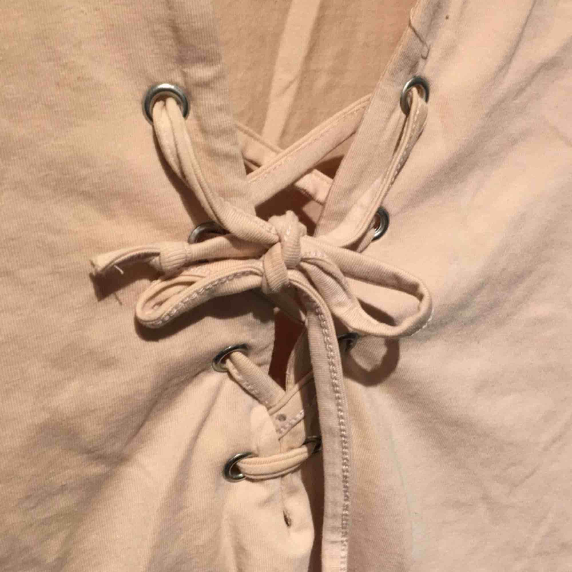 T-shirt med snörning vid bysten. Super fin beige/rosa färg. Använd fåtal gånger🌸. Toppar.