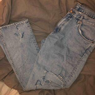 """Ett par ljusblåa jeans i modellen """"friday"""" ifrån weekday. Jeansen har slitningar på båda knäna och nere vid mudden av jeansen. Köpta för 600kr Köparen står för frakt 💚"""
