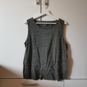 Grått linne med nitar Storlek: M Frakten ligger på 44 kr