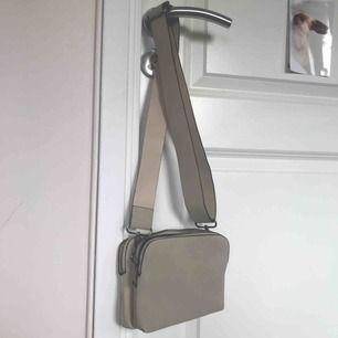 Snygg axelremsväska från Kappahl som tyvärr inte kommer till användning. Färgen är beige, den har två fack och en bred rem som går att justera i längden. Inga skador eller liknande, dvs mycket fint skick. Frakt ingår
