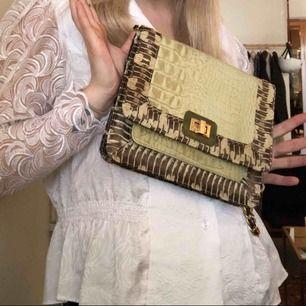 Angel Jackson väska, äkta läder i snakeprint, lite grön/gul i nyansen. Du kanske känner igen den från Blair i gossip girl som brukade ha dessa väskor! Köparen står för frakt själv :)