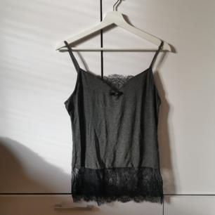 Grått linne med spetsdetaljer från New Yorker Storlek: M Frakten ligger på 22 kr