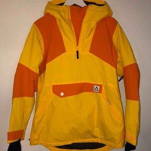 Skidjacka från Wearcolour i orange och gul färg. Använd en skidsäsong men i väldigt fint skick! (En liten fläck, syns på tredje bilden) Nypris ca 1600kr Frakt tillkommer! (Skriv till mig för fler bilder;))