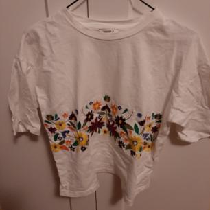 Fin vit t-shirt med broderade blommor på. Knappt använd och är därför i nyskick. Skriv gärna om du har några frågor.