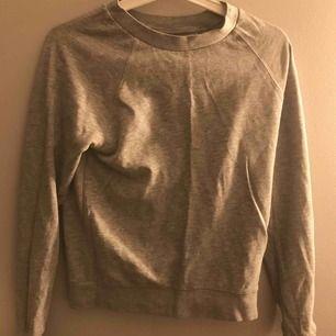 En långärmad grå tröja. Skön och väldigt snygg till ett par blåa jeans!