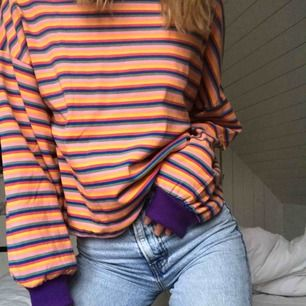 Färgglad sweater i skönt material. Aldrig använd, prislappen kvar. Lila muddar vid händerna och halsen. Frakt tillkommer