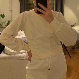 Superfin gräddvit tröja med snygg detalj under brösten