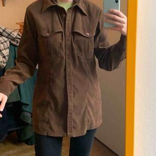 Brun skjorta som ger en sammet-känsla i tyget. Står storlek 38, kan tycka att den är liten i storleken. Kan även användas som en klänning (jag är 173 cm lång) Säljs billigt då det finns ett litet hål i kragen, syns knappt. Frakt 59kr