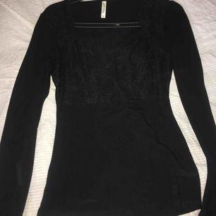 Svart tröja med spets detalj vid brösten. Köpt på Bubbelroom för 399 kr. Som ny! Figursydd.  Köparen står för frakten! Storlek XS