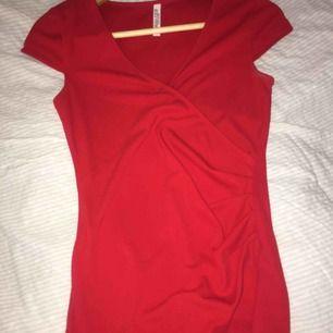 Röd topp, med snygg slits i sidan. Köpt på bubbelroom för 299 kr.