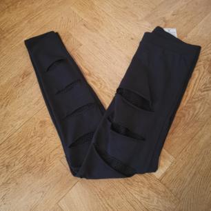 Svarta leggings med hål och nätdetaljer från New Yorker. Storlek: XS, men passar även S. Frakten ligger på 48 kr.