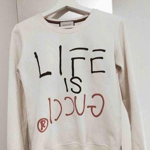 """""""Life is Gucci"""" sweatshirt i st. XS. Tjejtröja. Använd endast ett fåtal gånger och i super- skick. Köpt för 800 kr, säljs nu för 300 kr.  Kan mötas upp runt TC/ Sthlm city. Plagget är inte äkta. Superfin kvalité, knappt använd."""