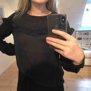 Söt mörkblå blus med en volang över bröstet ifrån Only. Säljs pga den inte används längre.