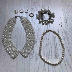 Paketpris för 8 smycken med konstgjorda pärlor: - pärlshalsband formad som en krage - Klassiskt pärlhalsband - Maffigt pärlarmband med stora pärlor - 4 guldmetallfärgade ringar - 1 par silverfärgade örhängen med en glaspärla.