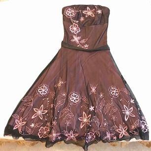 Rosa klänning med svart pådrag, broderade rosa blommor med pärlor, avtagbar svart band, bodyfitt upptill och volym nedtill.