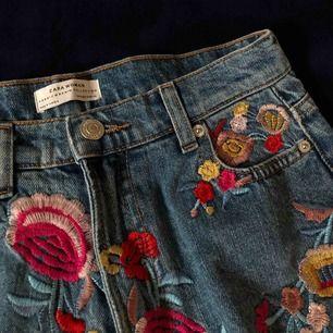 En jeanskjol från zara med blommor på. Köpt secondhand och är i bra skick!
