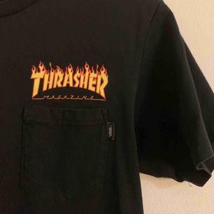 Thrasher x Vans T-shirt med as fett tryck back & en liten ficka fram, kommer inte till användning, den är som ny. Sitter mer som en M