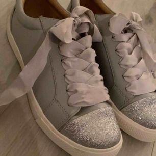 Gråa och silver glittriga skor i storlek 38, helt oanvända och säljer pågrund av att dom är för stora för mig och jag glömde att skicka tillbaka dom.