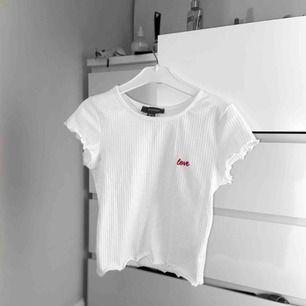 Kort vit topp från Primark i storlek 34 med ordet 'love' på bröstet! Otroligt söt och mysigt material! Fri frakt vid snabb affär! 🥀