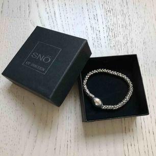 Helt nytt armband från SNÖ, aldrig använt. Säljes i sin orginalförpackning. Tex. En perfekt present!   Armbandet är elastiskt så flexibel storlek/passform.  Se bilder för mer detaljer & skick, zooma gärna & swipa för fler bilder.