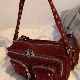 """Vinröd väska från núnoo i modellen """"ellie"""", väskan är i måtten 28x17x25.  Vanligt band och ett lite längre och dustbag medföljer. Den är köpt på Núnoos hemsida i sommars och är gott skick!🥰🥰 Nypris: 1495kr"""