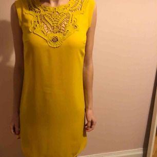 Gul, kort klänning med spets framtill, från Oasis. I gott skick.