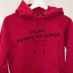 Väldigt fin hallonröd hoodie från Peak Performance med svart tryck, sparsamt använd och i väldigt bra skick. Storlek XS.