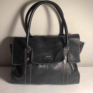 Rymlig, klassisk läderhandväska från Tiger of Sweden. Något skavd i hörnen.