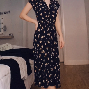 V-ringad midi-klänning från ASOS. Svart med ljust blommönster. Använd endast några få gånger.  Köparen betalar frakt.