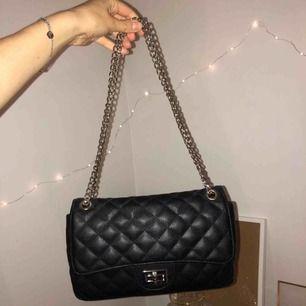 Svart väska med silverkedja, köpt på Nelly. Köparen står för frakt :)