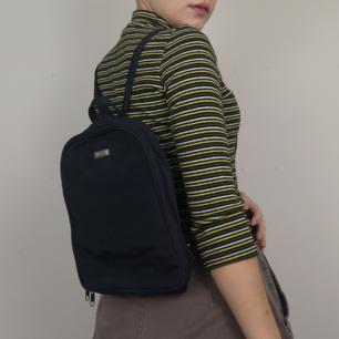 Superfin mindre ryggsäck i mörkblå färg, nästintill svart. Köpt secondhand men är så gott som i nyskick. Snygga randdetaljer i sömnaden fram och går att dra ihop banden med dragkejda så att ryggsäcken blir en axelremsväska istället. Är också ställbara band. Frakten för denna ligger på 63 kr, samfraktar gärna! 😊👍