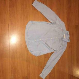 En ljusblå skjorta i en liten storlek, snygg till det nästa