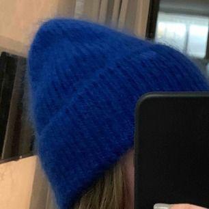 En blå mössa från Carin Wester. Använd ett fåtal gånger men är som ny.