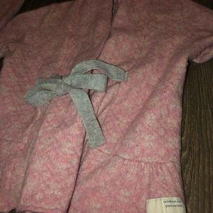 Detta är en rosa/vit stickad kofta, köpt för tre år sen men använd bara 4 gånger är i jätte bra skick!