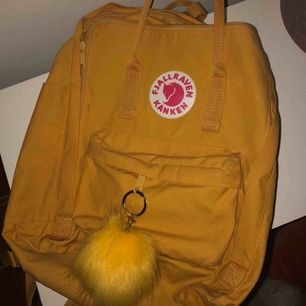 """Jätte fin Fjällräven ryggsäck i en härlig gul färg, nästan aldrig använd ( inga skador) tillkommer en jätte fin """"pom pom"""" ifrån GUESS. 120kr + frakt 🌙"""