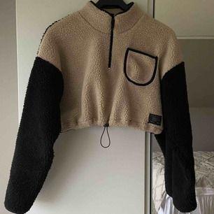 """Trendig beige/svart Teddy sweatshirt med ficka, dragkedja och går även att """"spänna"""" i midjan. Kortare i modellen. Använd 2 gånger. Nypris- 600 kr. Fraktkostnad 30 kr (köpare står för frakten)"""
