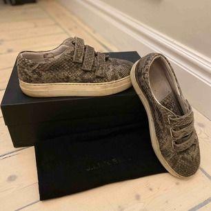 Gråa sneakers i ormmönster från J.Lindeberg, kartong och dustbag medföljer. De är i använt skick.