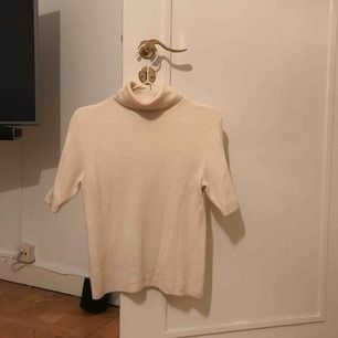 Kortärmad ribbad tröja med polokrage (gräddvit). Sticks ej