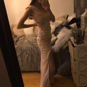 Aldrig använd klänning med fina detaljer i ryggen och slits. Fraktkostnad tillkommer