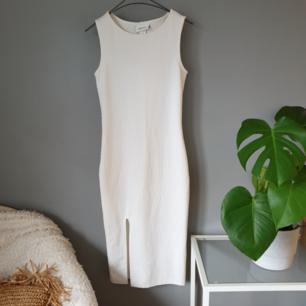 Vit klänning med slits framtill från Monki. Sparsamt använd.