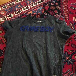 """En T-Shirt från Gamestop. Trycket """"Game boy"""" är i någon slags ull. Fraktas endast. Storlek S, köptes för 250 kronor."""