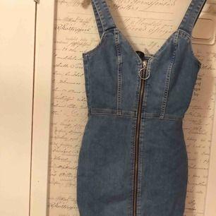 Jeansklänning/fodralklänning med en dragkedja från HM. Klänningen går att dra upp och den går ner låren. Oanvänd   (Köparen står för frakten)