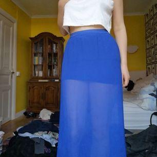 Somrig långkjol i ett genomskinligt tyg, med en kortare kjol under i samma färg. Går ner till ankeln på mig som är 168. Har klippt lappen men skulle tippa att den är storlek S. Köparen står för frakten!