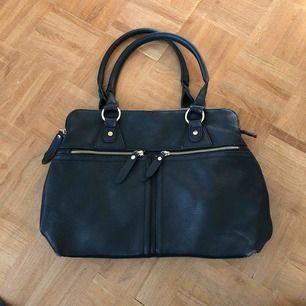 En svart väska med guld detaljer som får den att se lyxig ut. Inne i väskan så är det ett svart och vitt rutigt schack mönster som gör den väldigt cool. Finns många fack. Var min favorit väska men nu förtjänar den ett nytt liv. Köpt i Italien!!