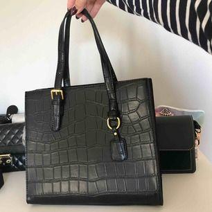 L: 26cm  B:21cm D:15cm . Vegansk svart väska med korkodilmönster och guldiga detaljer. Medföljer ett mörkbrunt axelband som tillhör väskan. Aldrig använd pga för liten. Jättefin väska att använda till vardags.